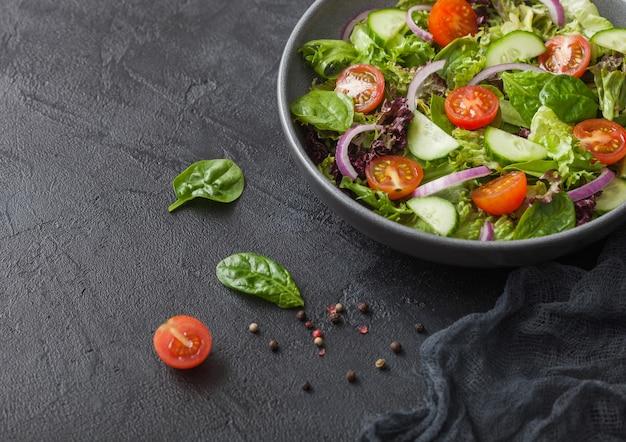 Ensalada de verduras frescas con lechuga y tomate, cebolla morada y espinacas en un tazón negro sobre fondo oscuro con una toalla de cocina
