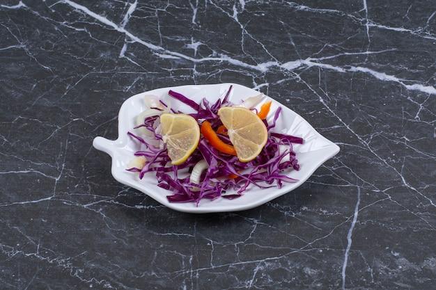 Ensalada de verduras frescas en un plato blanco sobre negro.