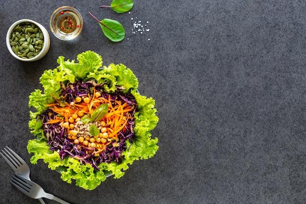 Ensalada de verduras frescas en un plato en negro. vista superior