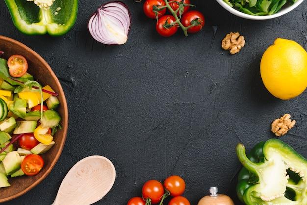 Ensalada y verduras frescas sobre encimera de cocina de concreto negro.