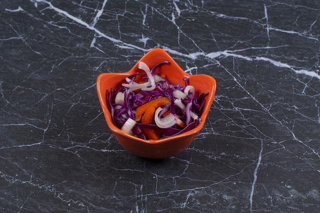 Ensalada de verduras frescas en un tazón de naranja sobre piedra negra.