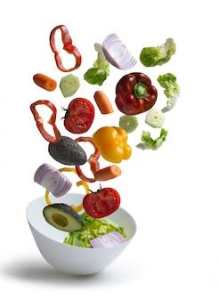 Ensalada de verduras frescas volando aislado