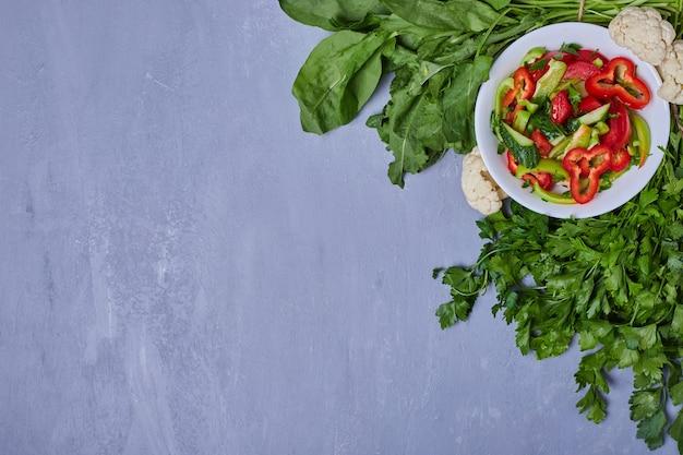 Ensalada de verduras con hierbas y especias en azul