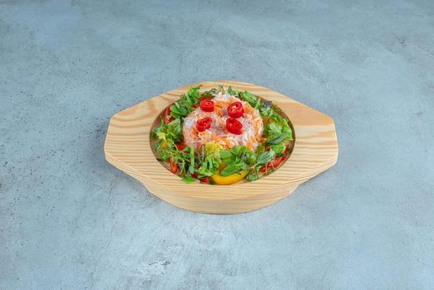 Ensalada de verduras con hierbas en un plato de madera.
