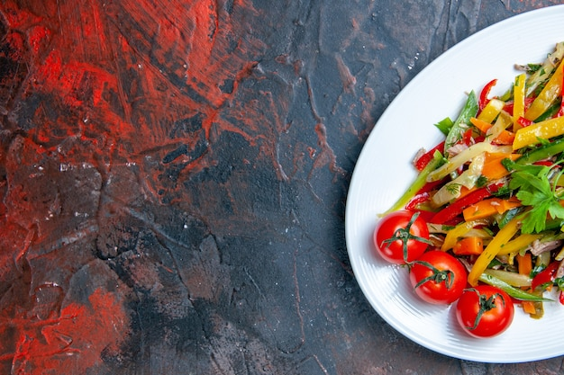 Ensalada de verduras de la mitad superior de la vista en un plato ovalado en el espacio libre de la superficie roja oscura