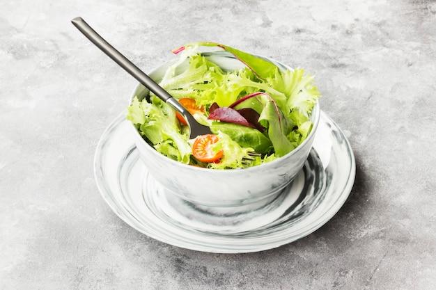 La ensalada de verduras mixtas y los tomates cherry en un recipiente sobre un fondo claro
