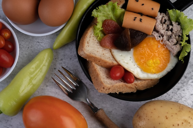 Ensalada de verduras con pan y huevos en la sartén.