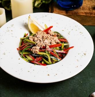 Ensalada de verduras con pepino, pimiento, pollo picado y limón en aceite de oliva.