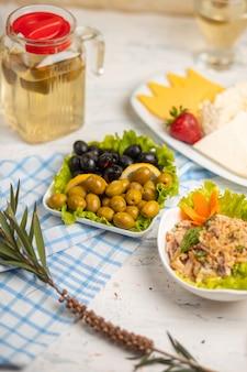Ensalada de verduras, pimiento, pollo con salsa dip y aceitunas