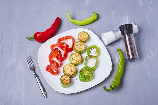 Ensalada de verduras en un plato blanco sobre azul
