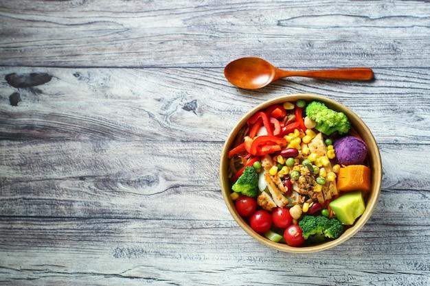 Ensalada de verduras y pollo en un tazón de papel sobre la mesa de madera