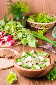 Ensalada de verduras de primavera en un plato de madera