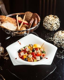 Ensalada de verduras con queso feta y aceitunas en un plato blanco