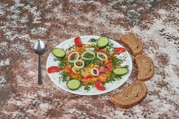 Ensalada de verduras con rebanadas de pan.