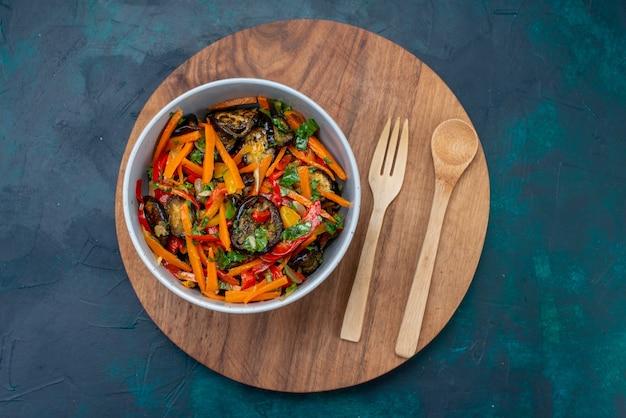 Ensalada de verduras en rodajas de vista superior dentro de la placa con cubiertos de madera en la superficie azul oscuro