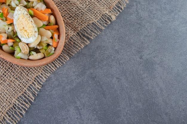 Ensalada de verduras en un tazón sobre una servilleta de arpillera sobre la superficie de mármol