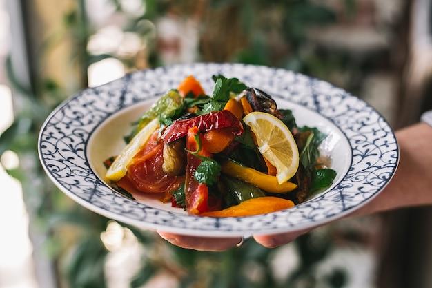 Ensalada de verduras con tomate, pimientos salteados, perejil, limón y aceite de oliva.
