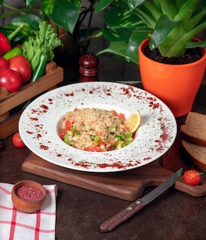 Ensalada de verduras, tomates, pepino con galletas. ensalada con sumakh y limón en la mesa de la cocina dentro de un plato blanco