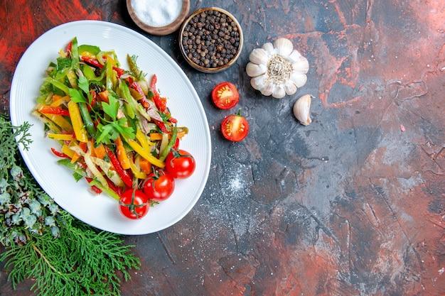 Ensalada de verduras de vista superior en placa ovalada tomates cherry especias de ajo en espacio libre de mesa rojo oscuro