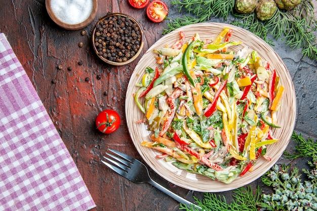 Ensalada de verduras vista superior en plato mantel tenedor sal y pimienta negra tomates ramas de pino en mesa rojo oscuro