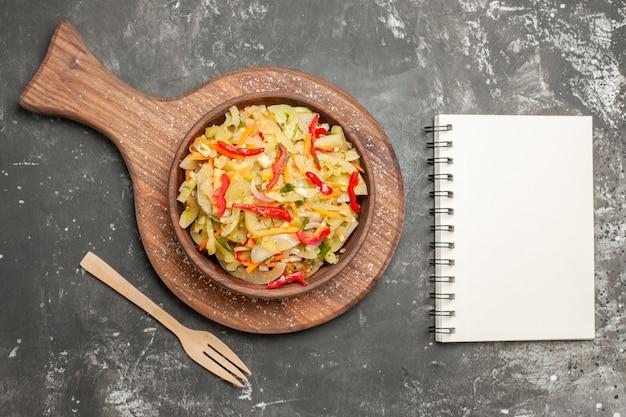 Ensalada de vista superior de cerca ensalada de verduras en la tabla de cortar junto al cuaderno de horquilla