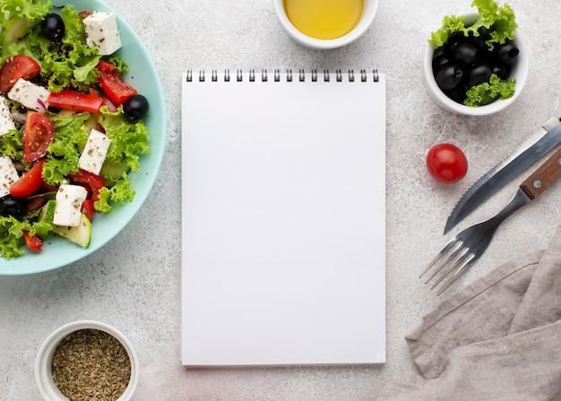 Ensalada de vista superior con queso feta, tomates y aceitunas con cuaderno en blanco