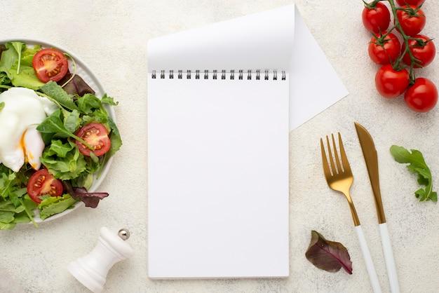 Ensalada de vista superior con tomates y huevo frito con bloc de notas en blanco