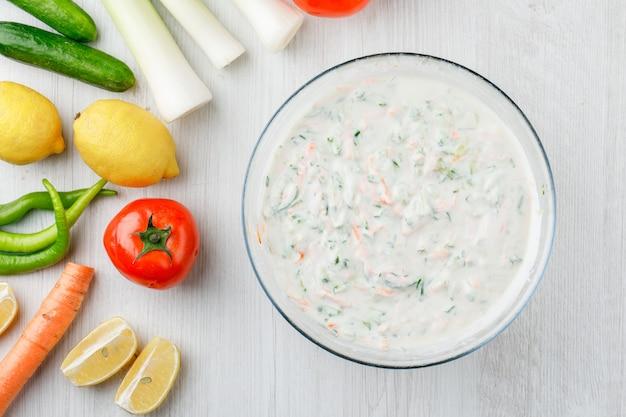 Ensalada de yogurt en un tazón con verduras y limones planos sobre una superficie de madera blanca