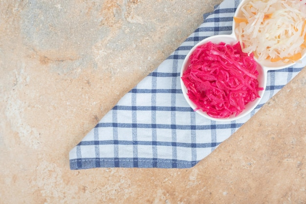 Ensaladas de chucrut rojo y blanco en tazones blancos con mantel