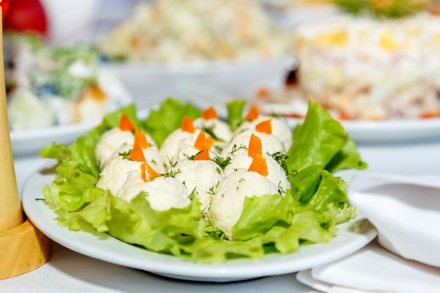Ensaladas en una mesa de banquete blanco