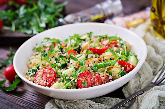 Ensaladas con quinoa, rúcula, rábano, tomates y pepino en un tazón sobre fondo de madera.