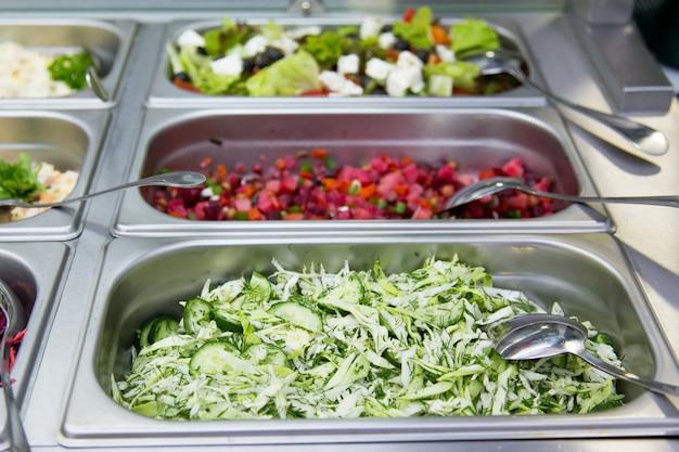 Ensaladas en restaurante sobre las placas de metal. enfoque selectivo