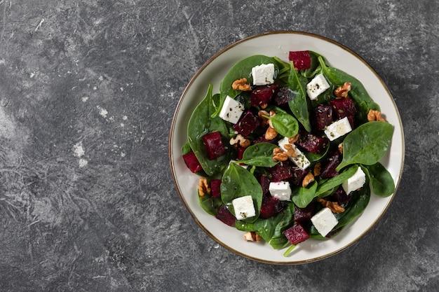Ensaladas vegetarianas de carpaccio de remolacha con espinacas, albahaca, aceite de oliva, queso de cabra, nueces. vista superior, espacio. alimentación saludable.