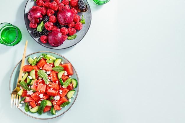 Ensaladas de verano con sandía y pepinos, bayas y helado.