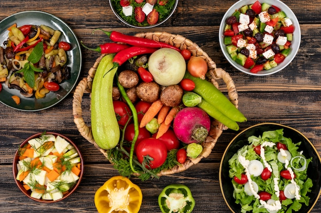 Ensaladas de verduras en concepto de vista superior de la mesa de madera