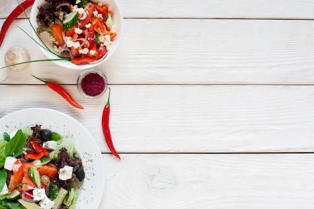 Ensaladas de verduras frescas en la mesa de madera blanca plana. vista superior de la mesa de la cocina con dos vegetarianos