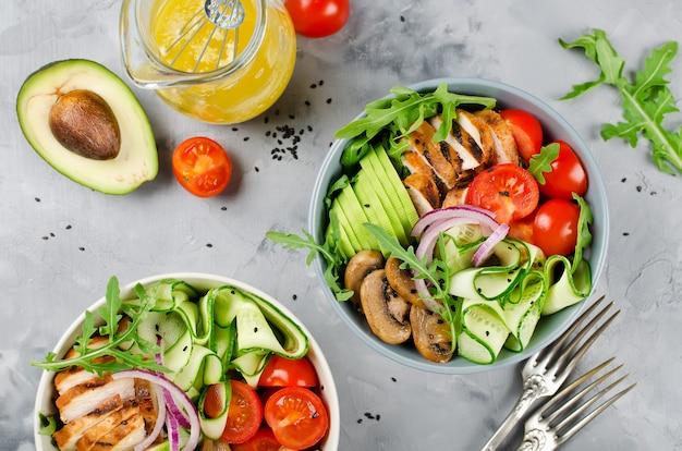 Ensaladera saludable con pollo, champiñones, tomates, pepinos, aguacate y rúcula