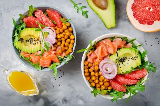 Ensaladera saludable con salmón, pomelo, garbanzos picantes, aguacate, cebolla roja y rúcula