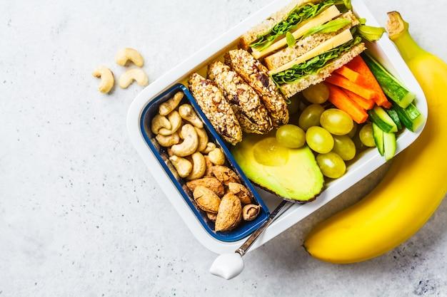 Enseñe la fiambrera sana con el bocadillo, las galletas, las frutas y el aguacate en el fondo blanco.