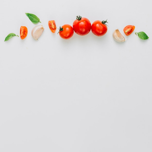 Entero y rebanada de tomates cherry; diente de ajo y albahaca sobre el fondo blanco