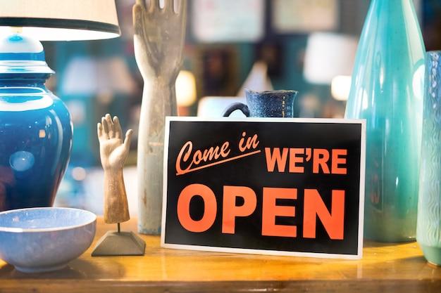 Entra estamos abiertos para negocios o signo comercial en un escaparate de una tienda o tienda apoyada contra coloridas cerámicas hechas a mano en primer plano