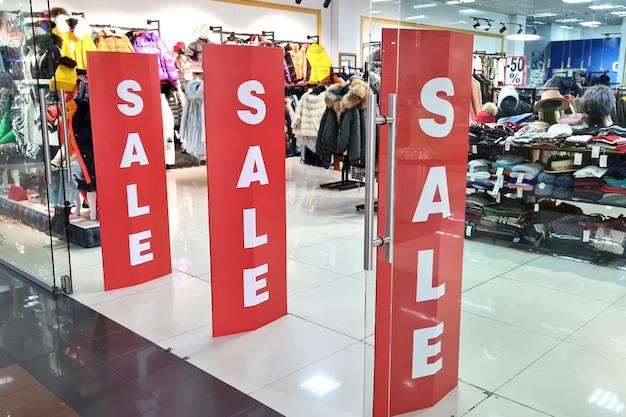 Entrada a la boutique de moda con carteles publicitarios de venta de ropa femenina en el centro comercial.