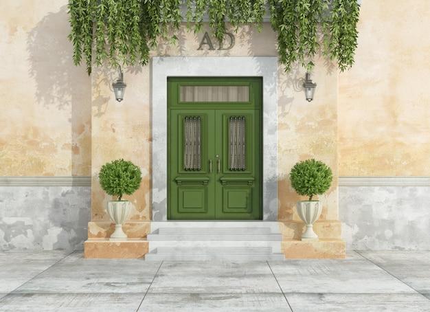 Entrada de una casa de campo con puerta verde clásica
