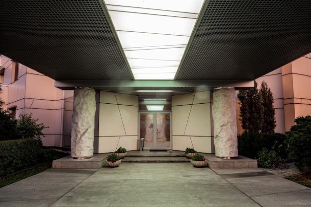 Entrada frontal cubierta al edificio con iluminación de columnas de piedra y parterres.