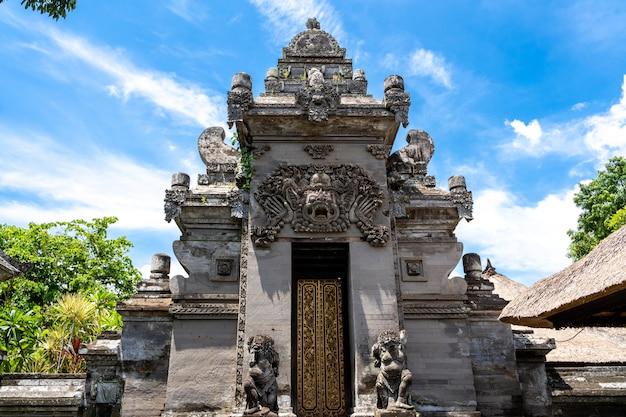 Entrada de piedra a un templo hindú con una puerta de madera