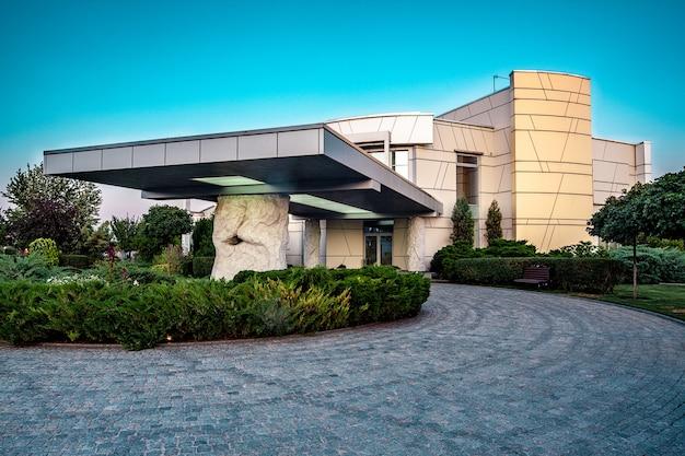 Entrada principal del hotel de lujo con porche sostenido por columnas rocosas y camino de acceso pavimentado