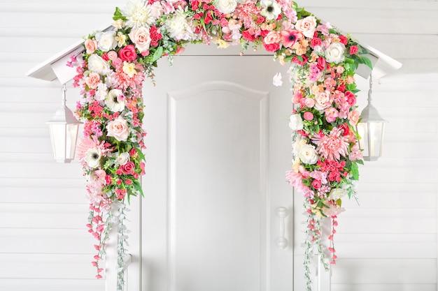 Entrada de puerta blanca, porche y alumbrado público. arco de flores. primavera.
