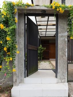 Entrada de valla de puerta de acero negro a casa con bloque de cemento y pasarela de piedras blancas