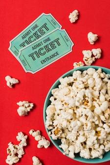 Entradas de cine al lado del bol con palomitas de maíz