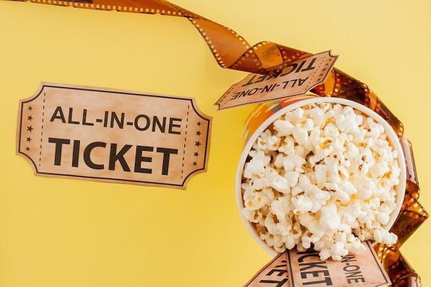 Entradas de cine, tiras de película y palomitas de maíz sobre fondo azul. copie el espacio para el texto.